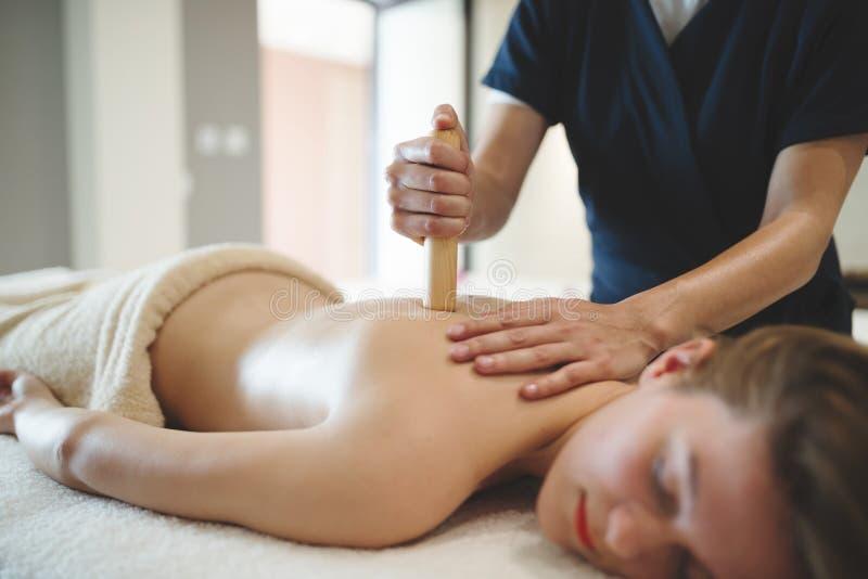 Massagista que usa varas e hastes para fazer massagens foto de stock royalty free