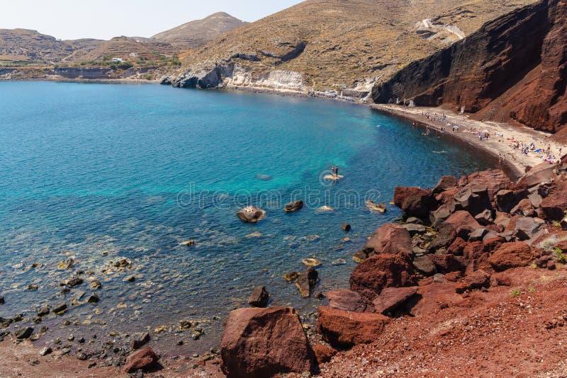 Massatoeristen die de zomer van vakantie in populair rood strand in Santorini, Griekenland genieten royalty-vrije stock foto's