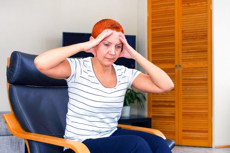 Masseer zijn tempels Een vrouw die aan een hoofdpijn lijden Gezondheidsproblemen, Vrouw die haar hoofd met haar hand houden stock foto's