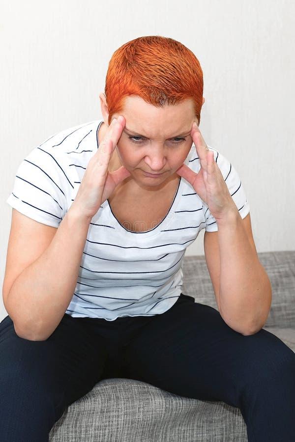Masseer zijn tempels Een vrouw die aan een hoofdpijn lijden Gezondheidsproblemen, Vrouw die haar hoofd met haar hand houden royalty-vrije stock afbeeldingen