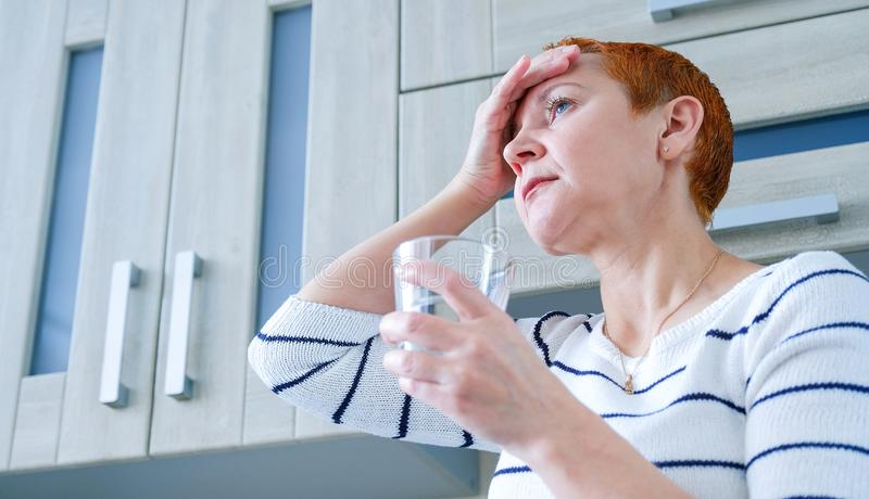 Masseer zijn tempels Een vrouw die aan een hoofdpijn lijden Gezondheidsproblemen, Vrouw die haar hoofd met haar hand houden stock afbeeldingen