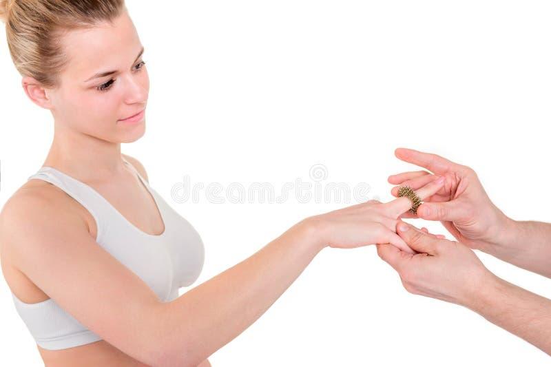 Massera handen med ett cirkelhjälpmedel Fysioterapeuten arbetar med a royaltyfri fotografi