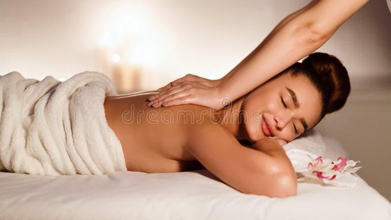 Masseur делая массаж на теле женщины в салоне курорта стоковые фотографии rf
