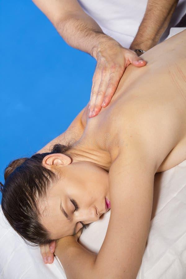 Masseur делая массаж на теле женщины в салоне курорта. Tre красоты стоковая фотография rf