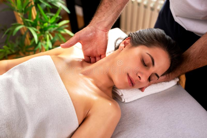 Masseur applying neck massage therapy. While his client rests stock image
