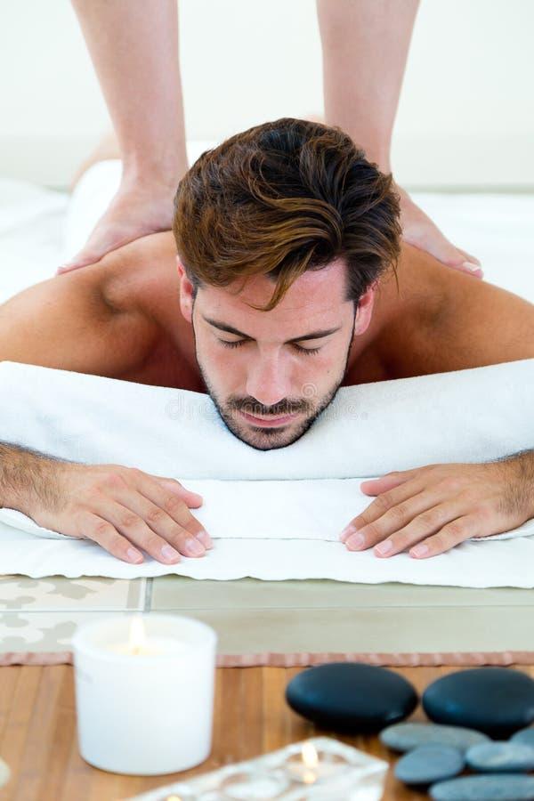 Masseur che fa massaggio sul corpo dell'uomo nel salone della stazione termale immagini stock libere da diritti