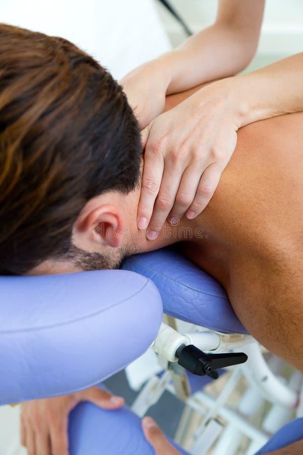 Masseur che fa massaggio sul corpo dell'uomo nel salone della stazione termale immagine stock
