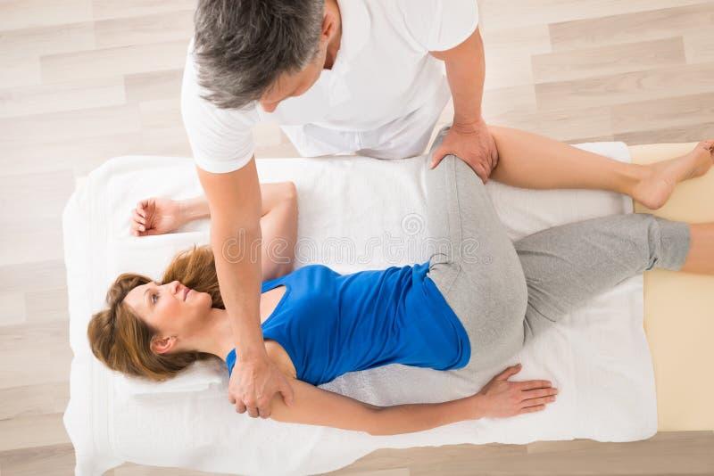 Masseur, der Massage auf Frau tut stockfoto