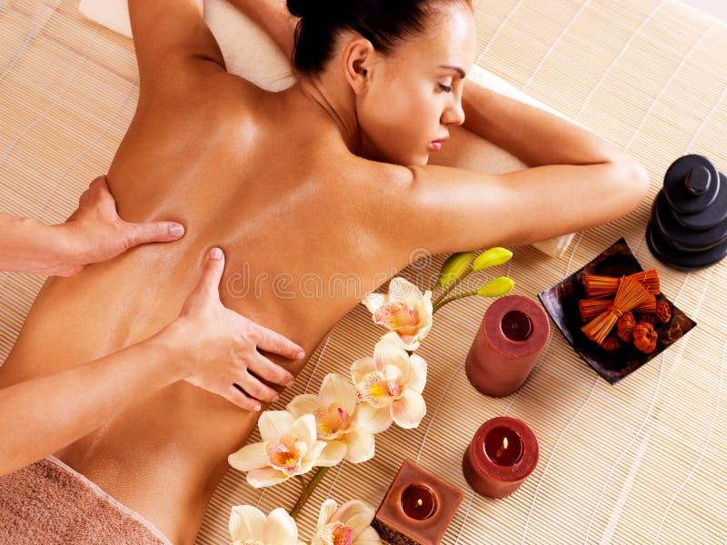 Masseur, der Massage auf Frauenrückseite im Badekurortsalon tut stockfoto