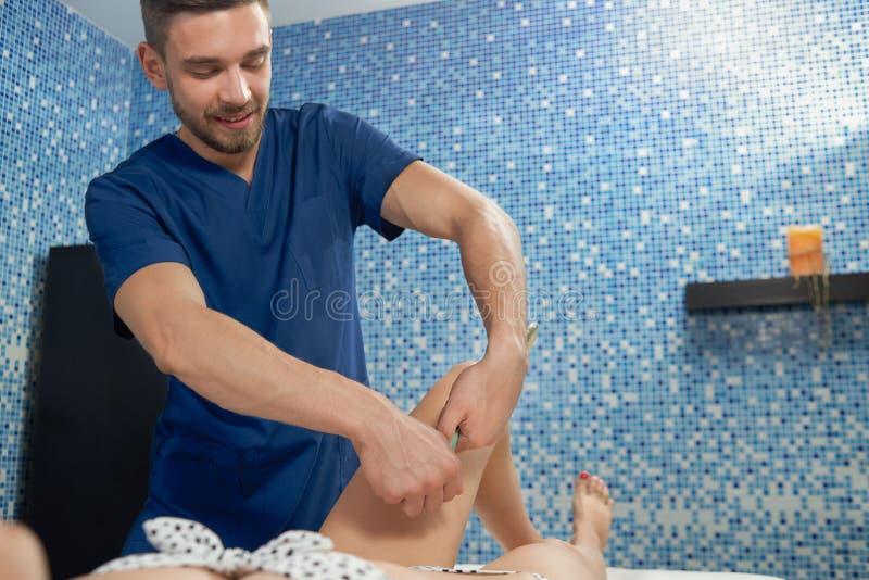 Masseur die anticellulite massage doen aan vrouw het liggen op laag royalty-vrije stock foto's