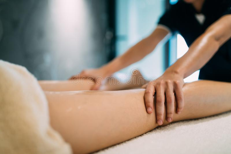 Masseur die masseuse masseren tijdens therapeutische tretment stock afbeeldingen