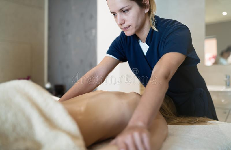 Masseur die terug van wijfje masseren stock foto