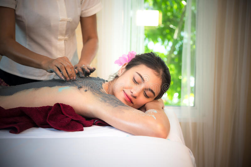 Masseur doing massage spa with treatment mud on Asian woman body in the Thai spa lifestyle, so relax and luxury. Masseur doing massage spa with treatment mud on stock photos