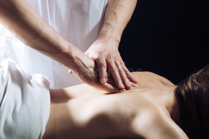 Masseur doing massage on woman body in the spa salon. Woman in spa salon, massage. Beauty treatment concept. Girl in spa royalty free stock photo