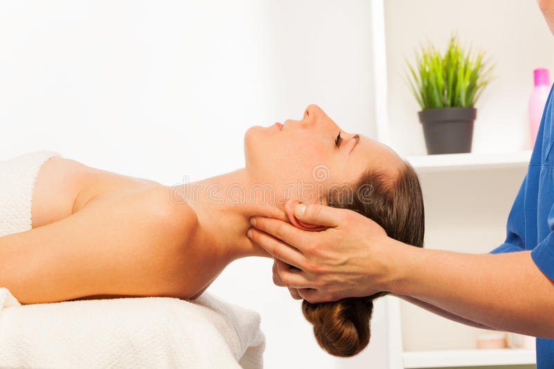 Masseur doing neck massage on woman in spa salon. Masseur doing neck massage on women laying on couch in the spa salon royalty free stock photos