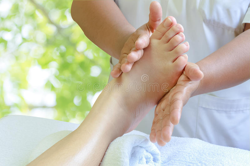 Masseur doing reflexology,Thai foot massage. In spa on nature background stock images