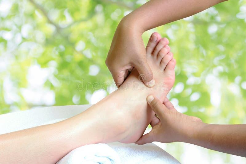 Masseur doing reflexology,Thai foot massage. In spa on nature background stock image