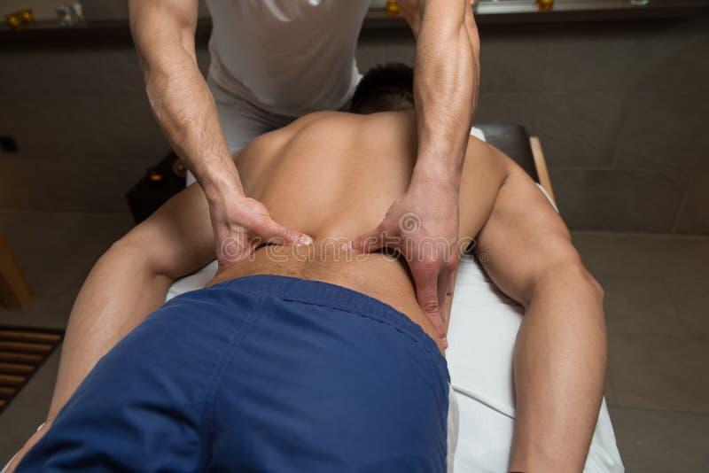 Masseur donnant le massage arrière à un homme photo stock