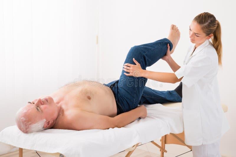 Masseur donnant le massage de jambe à l'homme image stock