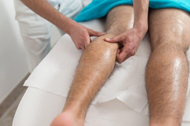 Masseur donnant le massage de jambes à un homme photos stock