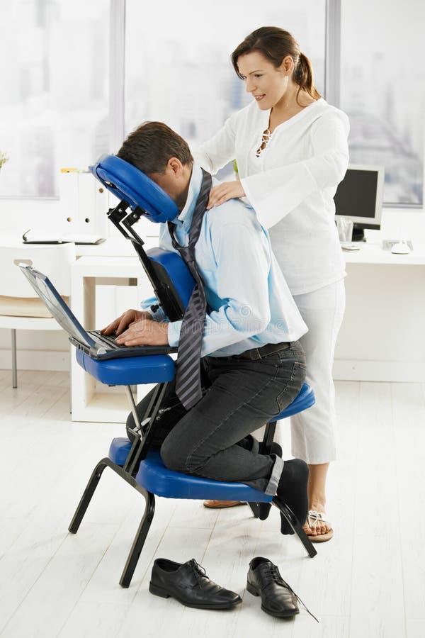 Masseur faisant le massage de cou dans le bureau image libre de droits