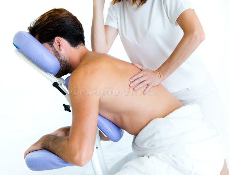 Masseur faisant le massage sur le fuselage de l'homme dans le salon de station thermale image libre de droits