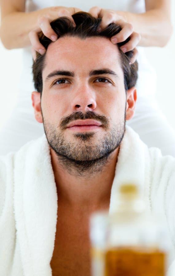 Masseur faisant le massage sur le fuselage de l'homme dans le salon de station thermale photographie stock