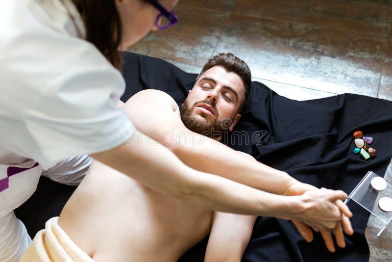 Masseur faisant le massage sur le fuselage de l'homme dans le salon de station thermale images libres de droits