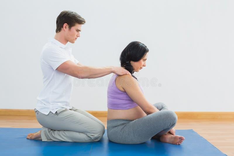 Masseur frottant les épaules de femme enceinte photographie stock libre de droits