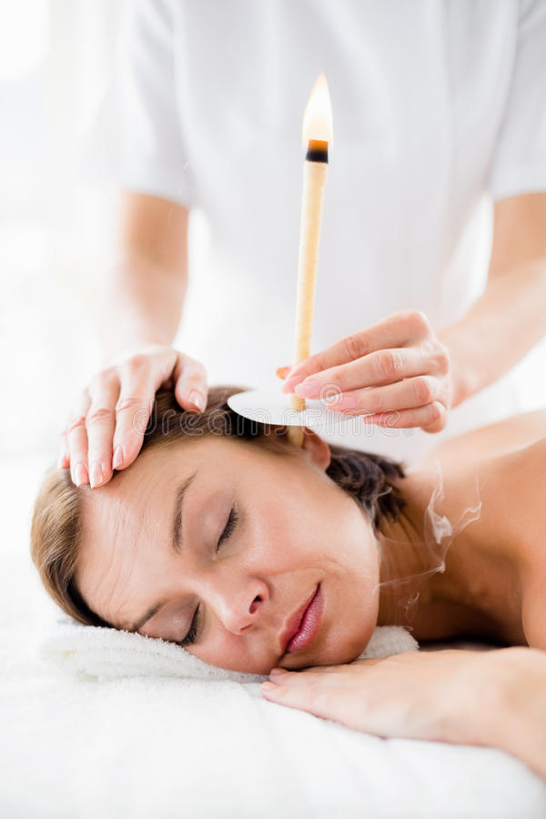 Masseur giving ear candle treament to woman stock photos