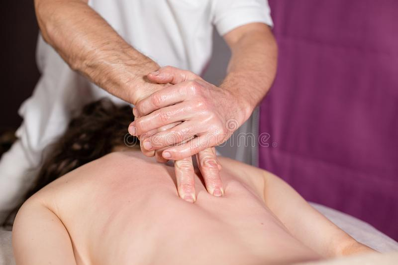 Masseur hands doing spine and back massage, neck and hand. Relaxed patient enjoys. Man hands massaging female. Spa stock photo
