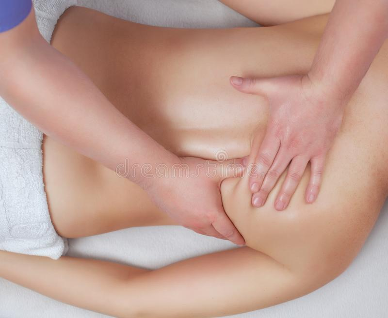 The masseur makes massage on the neck and back of the patient in the beauty salon. Medical assistance for the body royalty free stock images