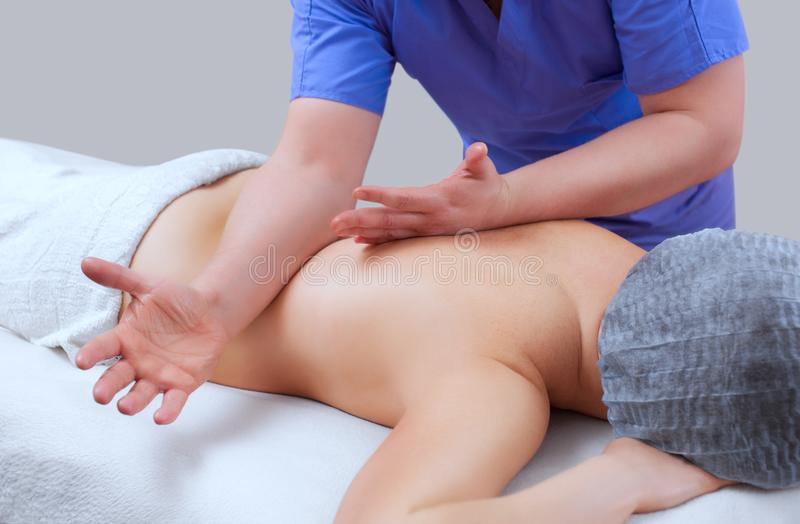 Masseur makes massage on the neck and back of the patient in the beauty salon. Medical assistance for the body. The masseur makes massage on the neck and back royalty free stock photography