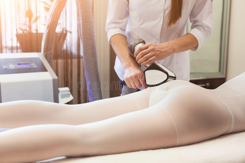 Masseur making hardware massage on patient`s legs in white suit. The masseur making an hardware massage on the patient`s legs in a white suit, in a beauty salon stock photo