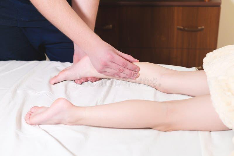 Masseur masculin en gros plan de physiothérapeute faisant un massage de détente curatif de pied à un petit enfant se trouvant sur photo stock