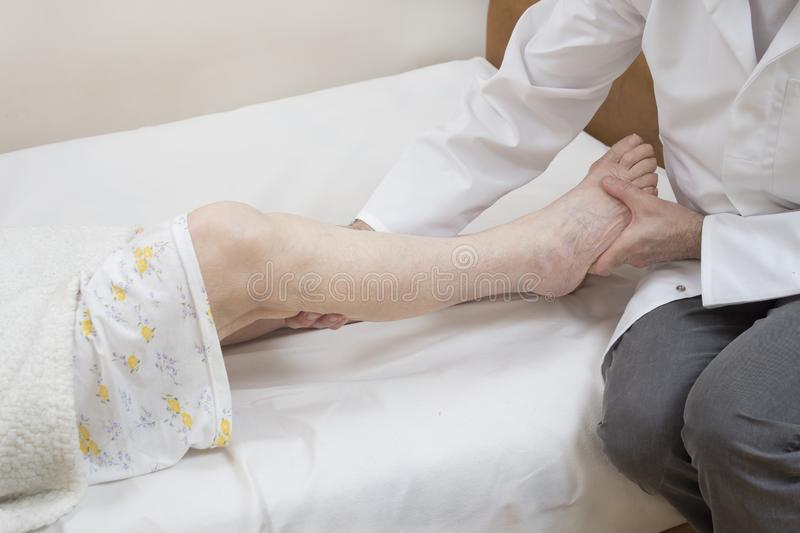 Masseur massages the calf of an old woman lying on a bed on a white sheet. stock photos