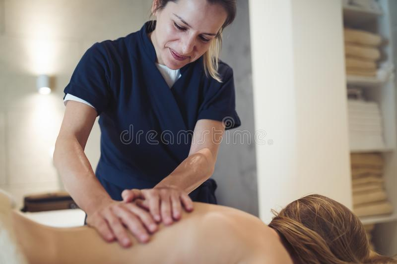 Masseur massaging back of female stock photo