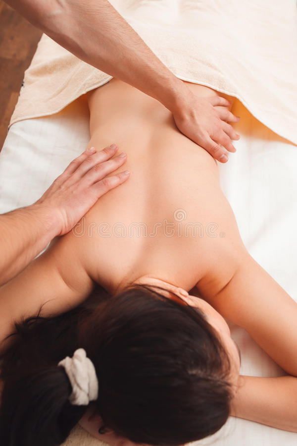 Masseur massaging female back top view stock photography