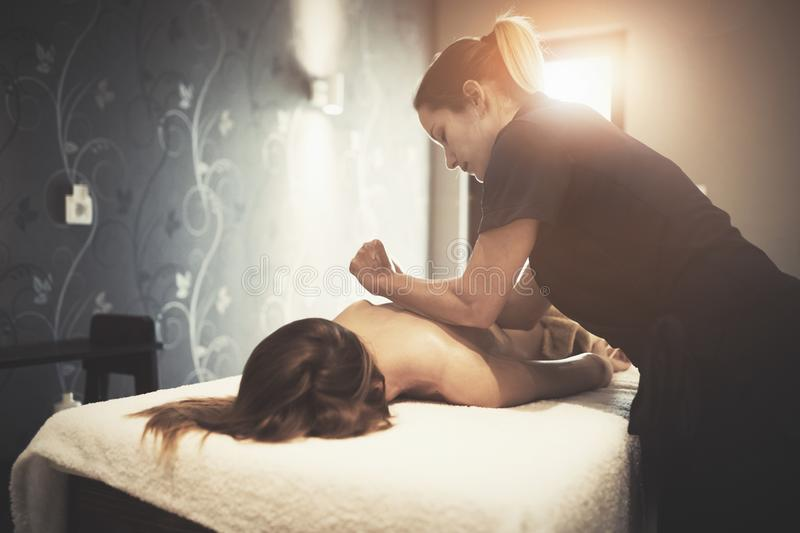 Masseur massaging female client at resort stock photos