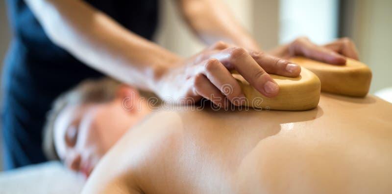 Masseur massant la masseuse à la station de vacances de bien-être image stock