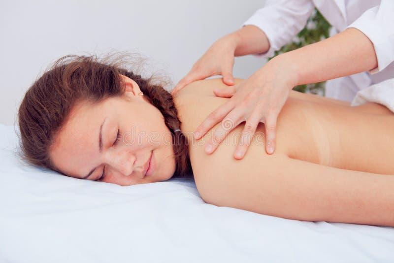Masseur que faz a massagem no corpo da mulher no salão de beleza dos termas Conceito do tratamento da beleza imagem de stock royalty free
