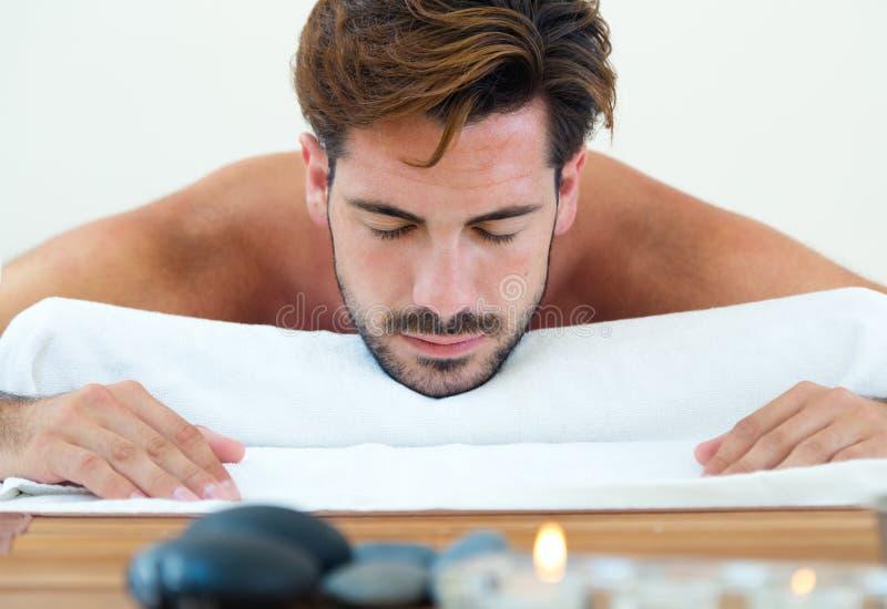 Masseur que faz a massagem no corpo do homem no salão de beleza dos termas foto de stock