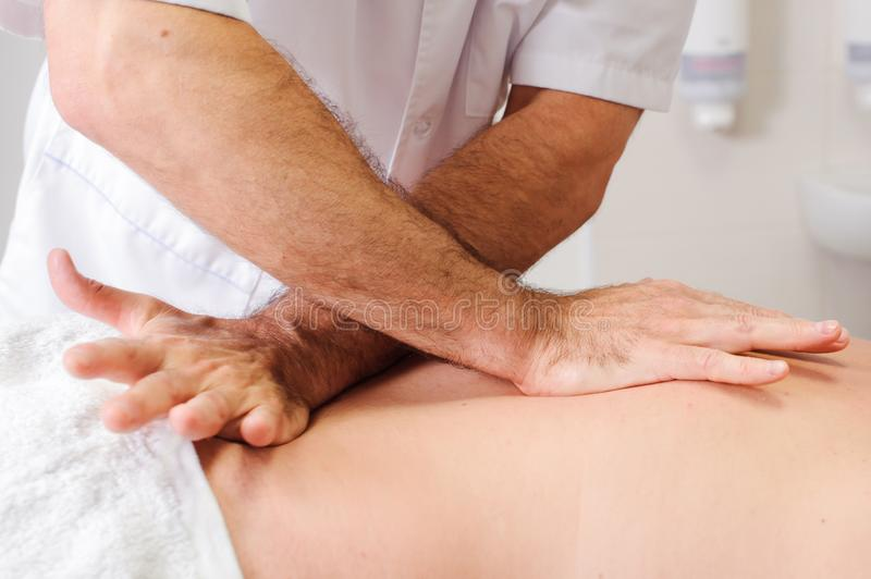 Masseur`s hands and a client back. Patient receiving a back massage by professional therapist stock images