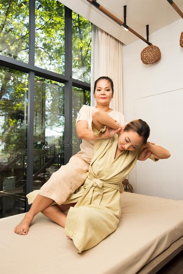 Masseuse étirant l'épaule de recourbement de massage de retour photos libres de droits