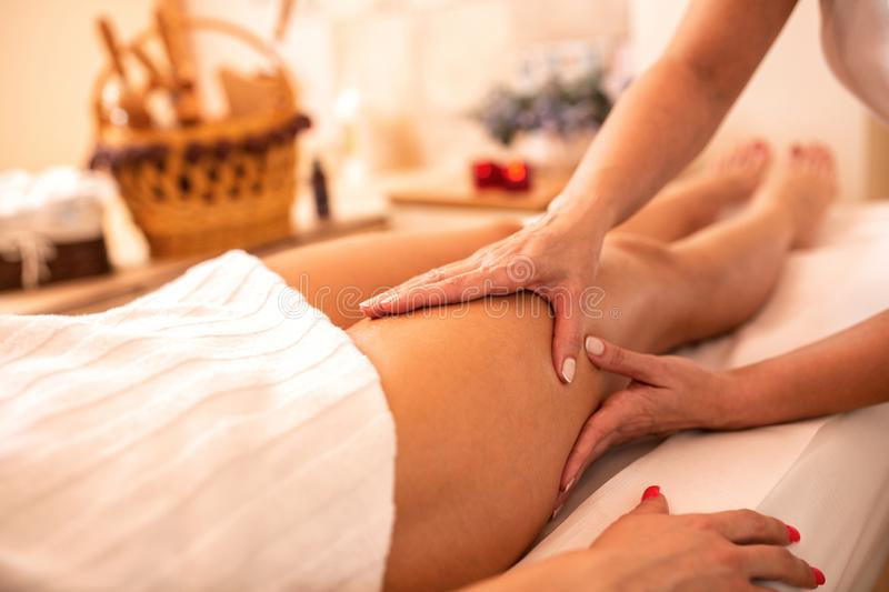 Masseuse applying her techniques on a woman's thigh stock photo
