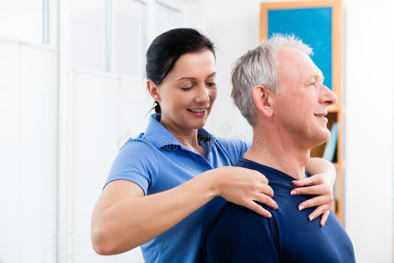 Physio giving shoulder massage to patient. Masseuse applying neck massage on older man royalty free stock photos