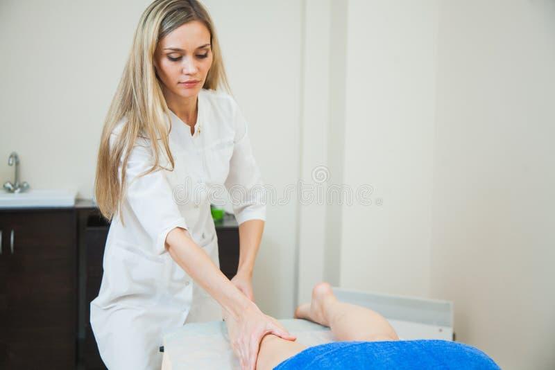 Masseuse d'esthéticien massant les jambes femelles, concept de bodycare photographie stock