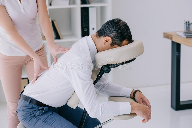 masseuse doing back massage on seat stock photos
