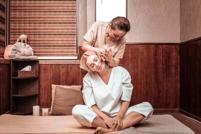 Masseuse doing neck and back massage for her client. Gifted hands. Concentrated smiling masseuse doing neck and back massage for her happy client sitting on the royalty free stock photography