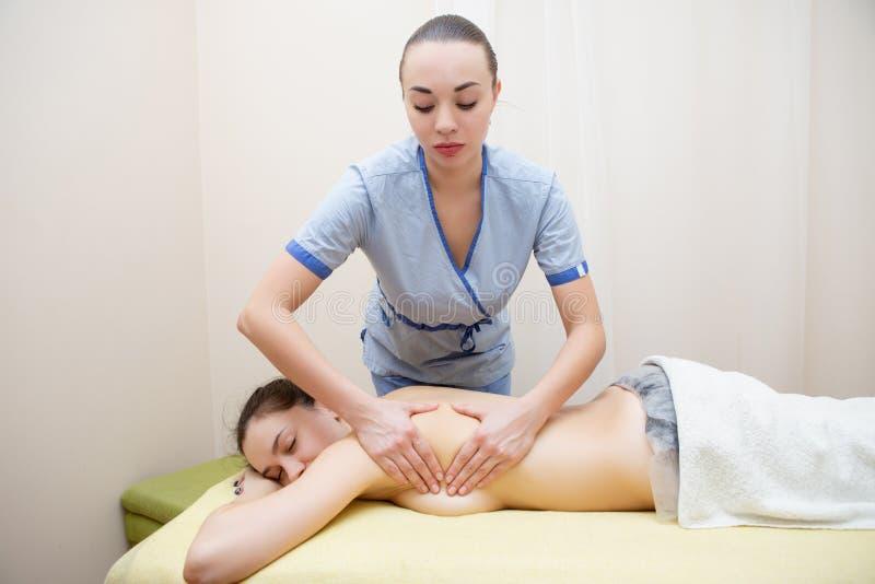 Masseuse gör massage till en söt brunett arkivfoton